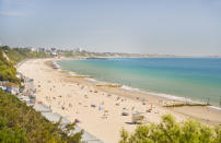 Enjoy seven miles of golden sands and some of the UK's warmest sea temperatures at this much-loved spot. While it might get busy during the sunny season, tourists come from afar to enjoy this bustling beach which is perfect for families and water sports enthusiasts alike. [Photo: Getty]