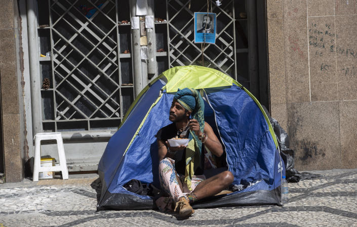 A homeless man eats food given to him by volunteers during a quarantine imposed by the state government to help contain the spread of the new coronavirus in Sao Paulo, Brazil, Monday, April 27, 2020. (AP Photo/Andre Penner)