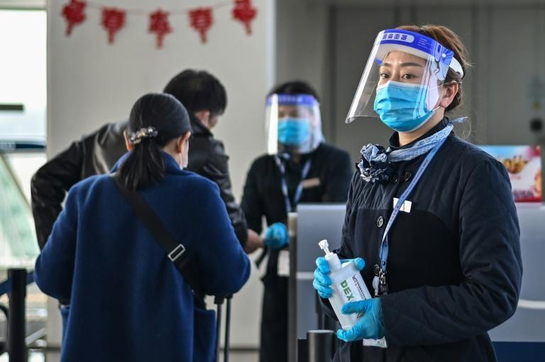 An airline worker at the international airport in Wuhan, China, is seen on February 12, 2021 offering passengers disinfecting gel; Wuhan was the epicenter of the Covid-19 pandemic but a WHO team was unable to determine the precise source