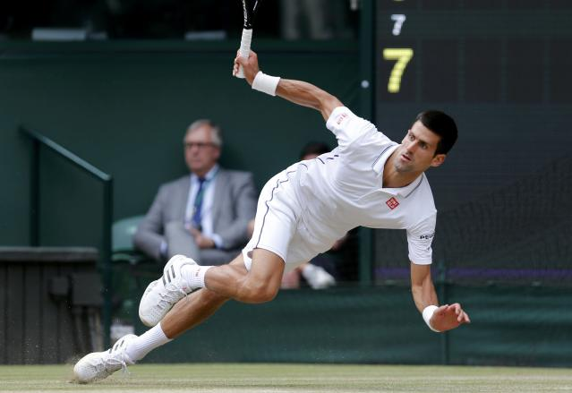 Novak Djokovic of Serbia slips during his men's singles final tennis match against Roger Federer of Switzerland at the Wimbledon Tennis Championships, in London July 6, 2014. REUTERS/Stefan Wermuth (BRITAIN - Tags: SPORT TENNIS TPX IMAGES OF THE DAY)