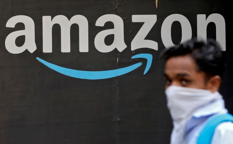 FILE PHOTO: FILE PHOTO: A man walks past an Amazon logo outside the company's collection point in Mumbai