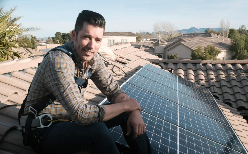 """This image released by Independent Lens shows Jonathan Scott from """"Property Brothers"""" installing solar panels on a rooftop in his new documentary """"Jonathan Scott's Power Trip."""" The film premieres Monday night as part of """"Independent Lens"""" on PBS stations across the country. (Neil Berkeley/Independent Lens via AP)"""