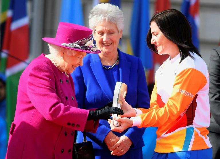 Retired Australian cyclist Anna Meares receives the baton from Britain's Queen Elizabeth II during the launch of the Queen's baton Relay for the XXI Commonwealth Games to be held in Gold Coast in 2018, in London, on March 13, 2017