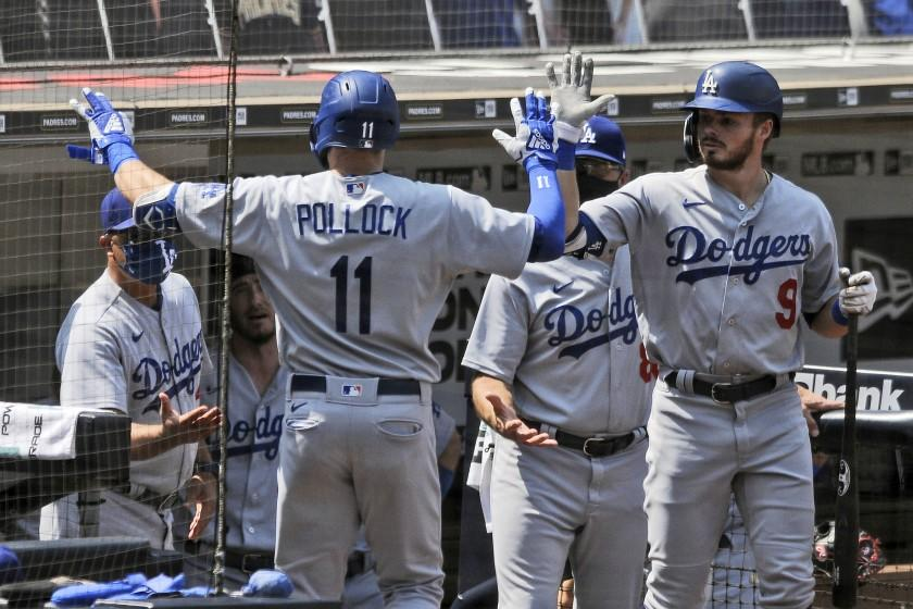 Los Angeles Dodgers' Gavin Lux, right, high-fives A.J. Pollock after Pollock hit a solo home run off San Diego Padres starting pitcher Adrian Morejon in the first inning baseball game Wednesday, Sept. 16, 2020, in San Diego. (AP Photo/Derrick Tuskan)