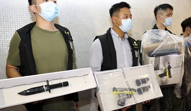 Hong Kong police show a haul of weapons, including a pistol-like pepper ball launcher, allegedly seized from the Fanling flat of 23-year-old Lui Sai-yu. Photo: Handout