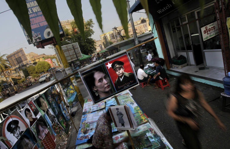 """In this photo taken, Thursday, Feb 23, 2012, people walk past a roadside stall selling the posters of Myanmar's democracy icon Aung San Suu Kyi and her late father Gen. Aung San at a market place in Yangon, Myanmar. Suu Kyi's once-banished image now appears everywhere, on T-shirts, keychains and coffee mugs. Pirated copies of """"The Lady"""", the big screen version of Suu Kyi's life, are the best-selling DVD on Yangon streets. (AP Photo/Altaf Qadri)"""