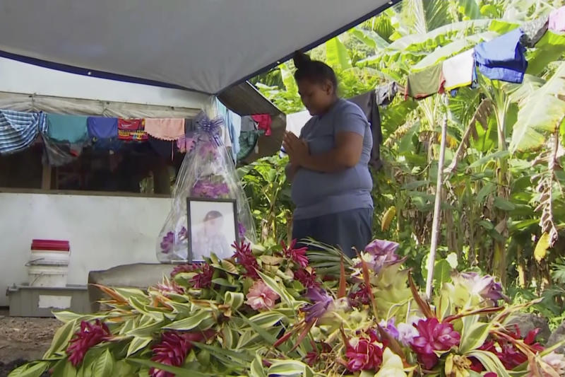 In this November 2019, image from video, a woman prays in front of a portrait of her lost child with measles in Apia, Samoa. Samoa closed all its schools on Monday, Nov. 18, 2019, banned children from public gatherings and mandated that everybody get vaccinated after declaring an emergency due to a measles outbreak. For the past three weeks, the Pacific island nation of 200,000 people has been in the grip of a measles epidemic that has been exacerbated by low immunization rates. (TVNZ via AP)