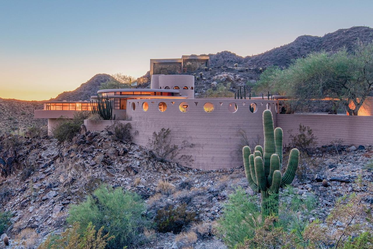 The home appears to be nestled in the rocky hillside. To avoid disturbing the desert landscape, each of the concrete blocks used to build the home was carried in by hand.