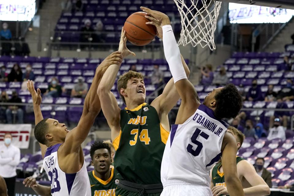 TCU forward Jaedon LeDee (23) and forward Chuck O'Bannon Jr. (5) combine to block a shot attempt by North Dakota State forward Rocky Kreuser (34) in the first half of an NCAA college basketball game in Fort Worth, Texas, Tuesday, Dec. 22, 2020. (AP Photo/Tony Gutierrez)
