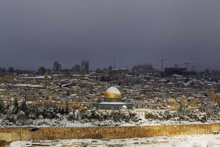 Snow covers the Dome of the Rock in the compound known to Muslims as Noble Sanctuary and to Jews as Temple Mount, in Jerusalem's Old City, as seen from the Mount of Olives February 20, 2015. Snow covered Jerusalem and mountainous areas of Israel early Friday morning and the education ministry closed schools for the day. (REUTERS/Ronen Zvulun)