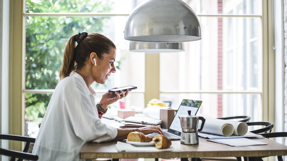 Woman on phone working from kitchen bench.