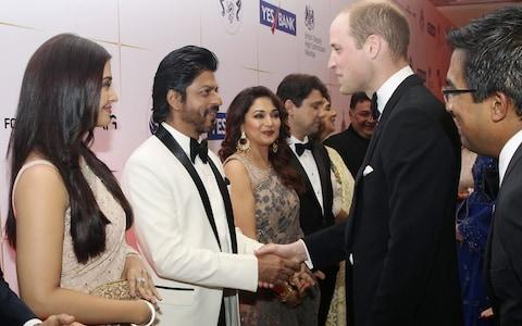 Britain's Prince William shakes hands with Bollywood actor Shah Rukh Khan - Credit: REUTERS/Rafiq Maqbool/Pool