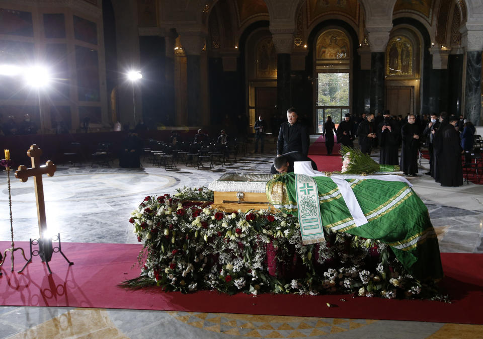 A man kisses the coffin of Patriarch Irinej during the funeral procession at the St. Sava Temple in Belgrade, Serbia, Sunday, Nov. 22, 2020. The 90-year-old Irinej died early on Friday, nearly three weeks after he led the prayers at a funeral of another senior church cleric in neighboring Montenegro, who also died after testing positive for the virus. (AP Photo/Darko Vojinovic)