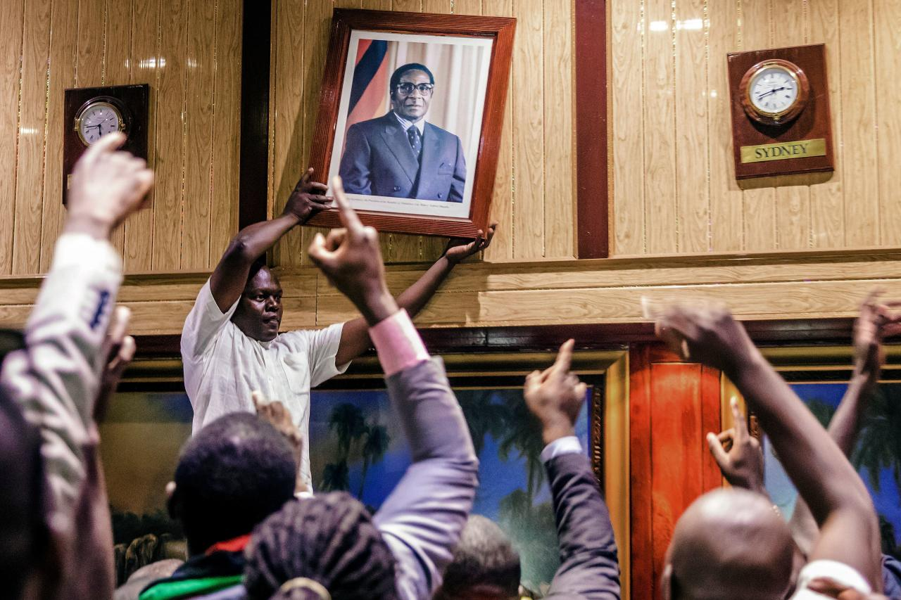 <p>People remove, from the wall at the International Conference centre, where parliament had their sitting, the portrait of former Zimbabwean President Robert Mugabe after his resignation on Nov. 21, 2017 in Harare. (Photo: Jekesai Njikizana/AFP/Getty Images) </p>