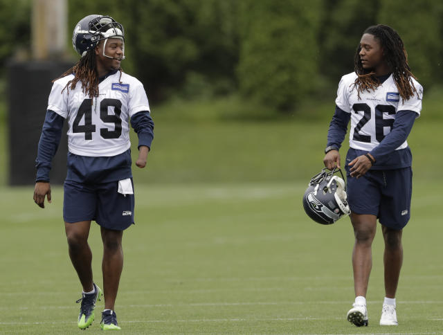 Seattle Seahawks linebacker Shaquem Griffin, left, walks with his twin brother, cornerback Shaquill Griffin, right, following NFL football practice, Thursday, June 14, 2018, in Renton, Wash. (AP Photo/Ted S. Warren)