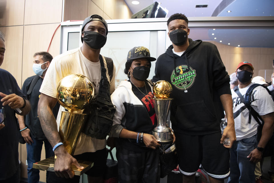 Giannis Antetokounmpo, right, NBA Champion of the Milwaukee Bucks, who was named NBA Finals Most Valuable Player, with his mother Veronica, and brother Thanasis pose for a picture at the Eleftherios Venizelos International Airport, in Athens, Greece, Sunday, Aug. 1, 2021. The NBA champion and finals MVP plans to stay in Greece for a few days, before returning to the U.S., where his girlfriend expects their second child later this month. (AP Photo/Michael Varaklas)