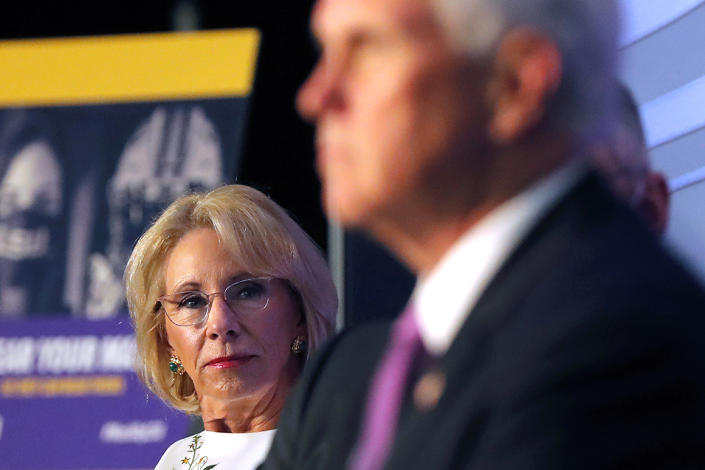 Education Secretary Betsy DeVos listens as Vice President Mike Pence speaks at a roundtable discussion in Tiger Stadium on the LSU campus.