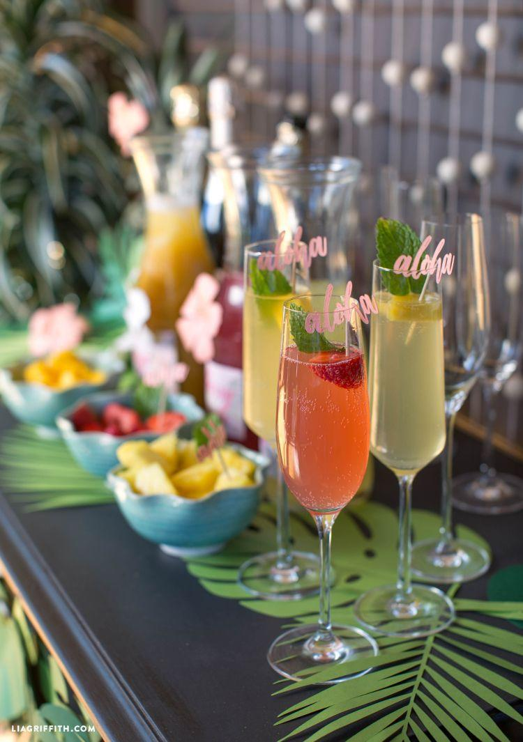 """<p>No matter where you actually are, you can feel like you're in the tropics with this mimosa bar theme. Decorate with palm leaves, add """"aloha"""" drink markers, and set up bowls with fresh cut pineapple, mango, and strawberry.</p><p>See more at <a href=""""https://liagriffith.com/tropical-bridal-shower-mimosa-bar/"""" rel=""""nofollow noopener"""" target=""""_blank"""" data-ylk=""""slk:Lia Griffith"""" class=""""link rapid-noclick-resp"""">Lia Griffith</a>.</p>"""