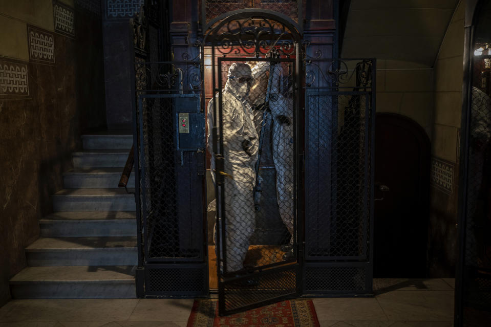Wearing protective suits to prevent infection, mortuary workers move the body of an elderly person who died of COVID-19 from an elevator after removing it from a nursing home in Barcelona, Spain, Friday, Nov. 13, 2020. (AP Photo/Emilio Morenatti)