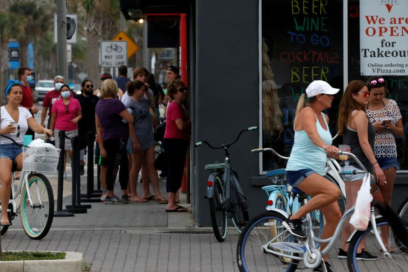 FILE PHOTO: People stand in line at a Duval County restaurant by the beach after it was opened amid coronavirus disease restrictions in Jacksonville