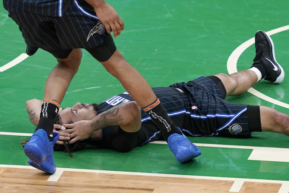 Orlando Magic guard Cole Anthony lies on the floor as teammate Khem Birch comes over to check on him during the second half of an NBA basketball game against the Boston Celtics, Friday, Jan. 15, 2021, in Boston. (AP Photo/Elise Amendola)