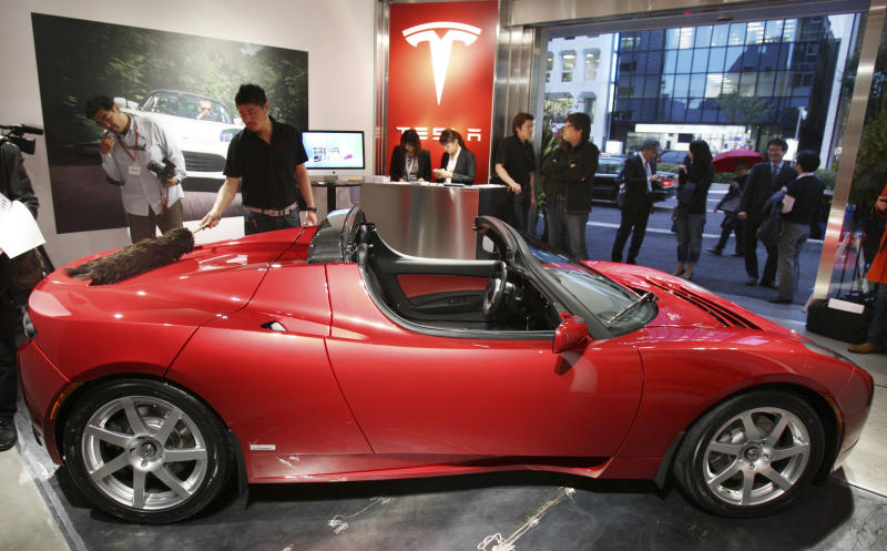 FILE - In this Oct. 25, 2010 file photo, a showroom worker cleans a Tesla electric roadster at Tesla's first Japanese showroom in Tokyo. Electric car maker Tesla Motors Inc. said Wednesday, May 25, 2011, it plans to raise up to $214.3 million in private and public placements to develop its Model X electric crossover vehicle. (AP Photo/Koji Sasahara, File)