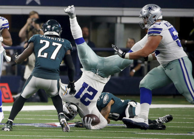 Philadelphia Eagles' Malcolm Jenkins (27) and Dallas Cowboys' Connor Williams, right, look on as running back Ezekiel Elliott, center, is upended by Eagles cornerback Orlando Scandrick, bottom rear, in the second half of an NFL football game in Arlington, Texas, Sunday, Oct. 20, 2019. (AP Photo/Ron Jenkins)