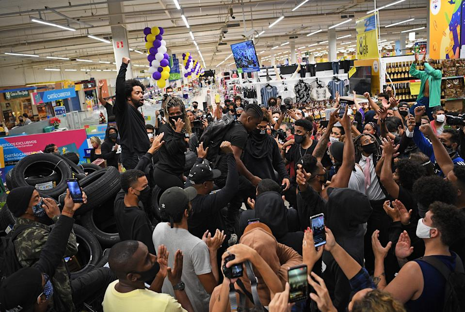 Demonstrators make a barrier out of car tyres as they take part in a protest inside the supermarket Carrefour in Rio de Janeiro, Brazil, on November 20, 2020 on Black Consciousness Day, against the death of a black man inside a supermarket of the same chainin Porto Alegre. - The death on Thursday night of Joao Alberto Silveira Freitas after being beaten by white security agents in a supermarket belonging to the Carrefour group in Porto Alegre unleashed a wave of indignation in Brazil. (Photo by Carl DE SOUZA / AFP) (Photo by CARL DE SOUZA/AFP via Getty Images)