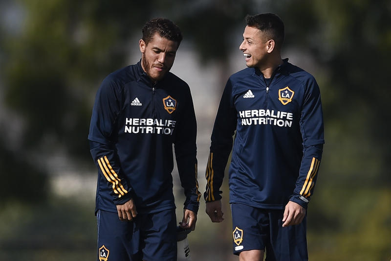 """Los Angeles Galaxy's Javier """"Chicharito"""" Hernndez, right, speaks with Jonathan dos Santos during a practice in Carson, Calif., Thursday, Jan. 23, 2020. (AP Photo/Kelvin Kuo)"""