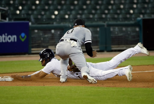 Chicago White Sox third baseman Yoan Moncada, top, tags out Detroit Tigers' Victor Reyes, bottom, at third base in the seventh inning of a baseball game in Detroit, Monday, Aug. 10, 2020. (AP Photo/Paul Sancya)