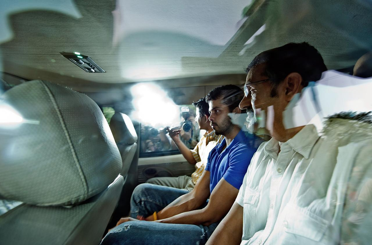 Indian cricketer Shanthakumaran Sreesanth (R) is escorted in a police vehicle on his way to court in New Delhi on May 21, 2013.  India's Test paceman Shanthakumaran Sreesanth and two other bowlers were to appear in court over allegations that they accepted tens of thousands of dollars for spot-fixing, police said.    AFP PHOTO/ MANAN VATSYAYANA