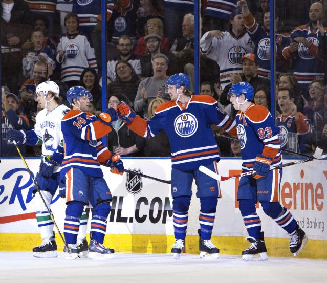 Vancouver Canucks' David Booth (7) skates past as Edmonton Oilers' Jordan Eberle (14), Jeff Petry (2) and Ryan Nugent-Hopkins (93) celebrate a goal during first period NHL hockey action in Edmonton, Alberta, on Saturday April 12, 2014. (AP Photo/The Canadian Press, Jason Franson)