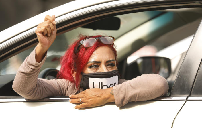 Rideshare driver Teresa Mercado raises her fist in support in a protest urging voters to vote no on Proposition 22 (Al Seib / Los Angeles Times