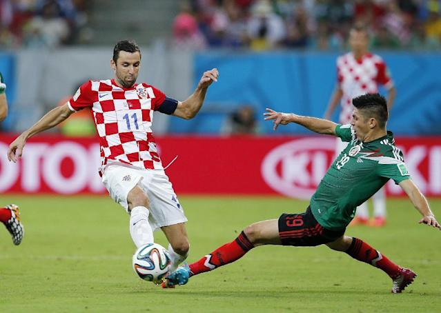 Mexico's Oribe Peralta, right, fights for the ball with Croatia's Darijo Srna during the group A World Cup soccer match between Croatia and Mexico at the Arena Pernambuco in Recife, Brazil, Monday, June 23, 2014. (AP Photo/Eduardo Verdugo)
