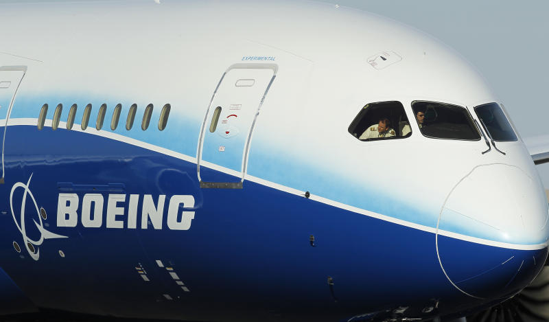 """Capt. Randy Neville, left, a Boeing 787 test pilot, looks out the cockpit window as his Boeing 787 Dreamliner jumbo passenger jet taxis on the tarmac at Phoenix Sky Harbor Airport, Friday, March 9, 2012, in Phoenix.  Phoenix area Honeywell Aerospace workers were able to get a peek at the new plane that the company supplied a dozen systems for, including flight management, navigation and communications.  The 787 uses lighter carbon fiber for half its construction and is much more fuel-efficient than older planes.  Boeing has been sending its """"Dream Tour"""" airplane to airports around the world since late last year. The jet's cabin features larger dimmable windows, bigger overhead bins and dynamic LED lighting.(AP Photo/Ross D. Franklin)"""