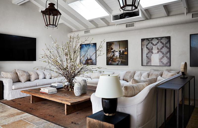 In the poolhouse, a sofa wraps around a custom reclaimed-wood cocktail table. Indian textiles cover the pillows.