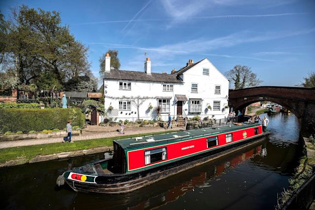 A houseboat passes along the Bridgewater canal at Lymm in Cheshire. Photo: Peter Byrne/PA Images via Getty Images