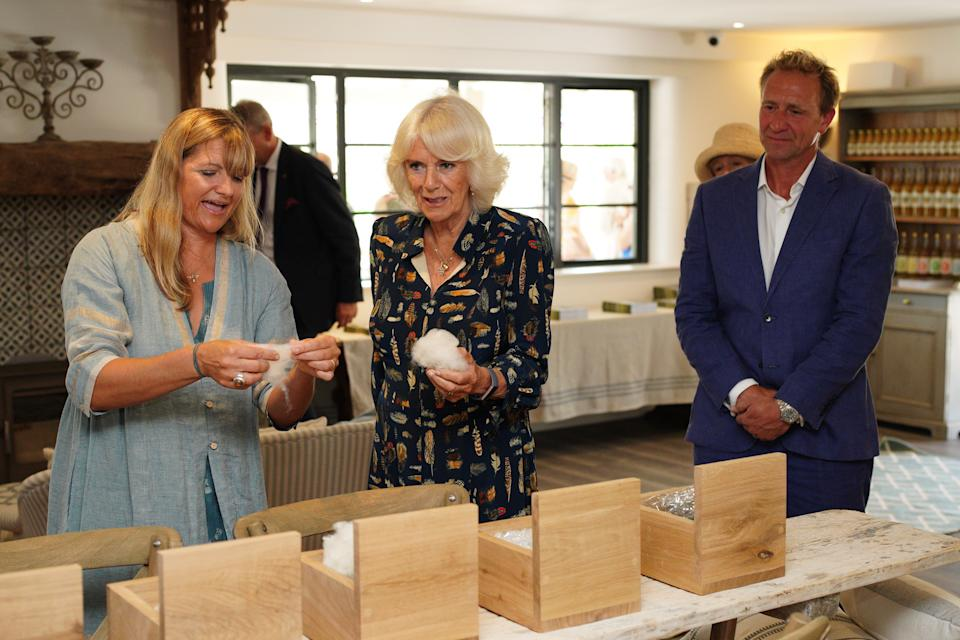 The Duchess of Cornwall meeting owners Tasha and Barney Green during a visit to the new Weaver Green showroom at Heron Valley Orchards, in Loddiswell, Devon, to learn how the company creates homewares from recycled plastics and meet local school children learning about wildlife and sustainability. Picture date: Monday July 19, 2021.