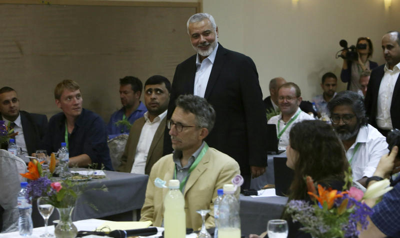 Hamas' chief Ismail Haniyeh, center, arrives to a meeting with foreign reporters at al-Mat'haf hotel in Gaza City, Thursday, June 20, 2019. Hamas' chief says Israel is ignoring the terms of an indirect cease-fire agreement for the Gaza Strip. (AP Photo/Adel Hana)