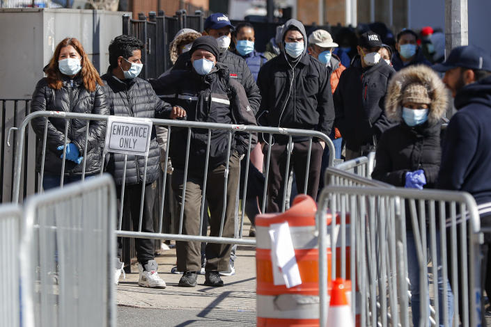 Patients wearing face masks and personal protective equipment wait on line for COVID-19 testing outside Elmhurst Hospital Center, Friday, March 27, 2020, in New York. (AP Photo/John Minchillo)