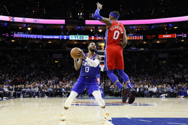 Los Angeles Clippers' Paul George, left, tries to get a shot past Philadelphia 76ers' Josh Richardson during the first half of an NBA basketball game, Tuesday, Feb. 11, 2020, in Philadelphia. (AP Photo/Matt Slocum)