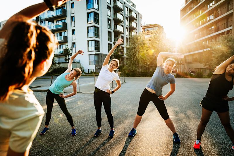 An urban fitness group for women warming up before a run through the city together.