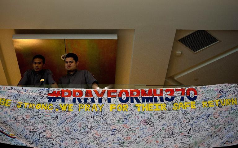 Hotel staff stand next to a banner expressing wishes and prayers for the missing of flight MH370, at the Everly hotel in Putrajaya where some relatives have gathered