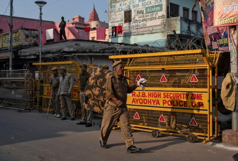 A police officer walks past a security barricade as others stand guard near a temple after Supreme Court's verdict on a disputed religious site, in Ayodhya
