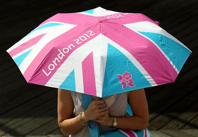 A woman holds a London 2012 branded umbrella at the launch of the London Olympic Games official merchandise on July 30, 2010 in London, England. The merchandise is being launched with two years to go before the Games begin and features a range of goods including: clothing, towels, bedding, ceramics, stamps, coins, badges, mascot toys and soft furnishings. (Photo by Oli Scarff/Getty Images)