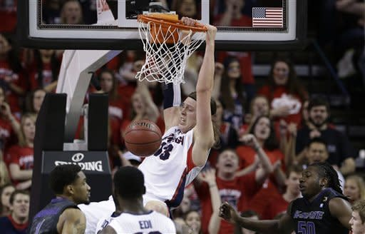 Gonzaga's Kelly Olynyk hangs on the rim for a few moments after dunking against Kansas State in the first half of an NCAA college basketball game Saturday, Dec. 15, 2012, in Seattle. (AP Photo/Elaine Thompson)