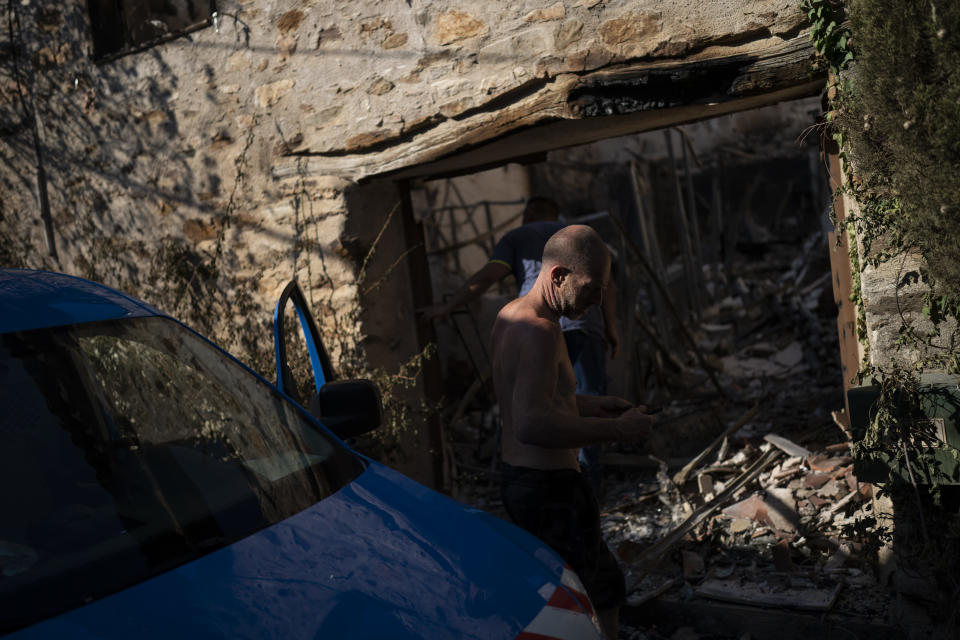 A resident inspects damage caused by wildfires in Val de Gilly, southern France, Thursday, Aug. 19, 2021. A fire that has ravaged forests near the French Riviera for four days is slowing down as winds and hot weather subside, but more than 1,100 firefighters were still struggling to get it under control Thursday, local authorities said. (AP Photo/Daniel Cole)