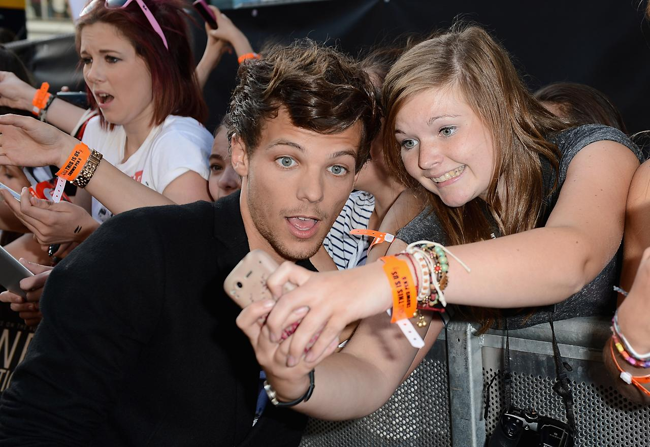 "LONDON, ENGLAND - AUGUST 20:  Singer Louis Tomlinson from One Direction poses with fans as he attends the ""One Direction This Is Us"" world premiere at the Empire Leicester Square on August 20, 2013 in London, England.  (Photo by Ian Gavan/Getty Images for Sony Pictures)"