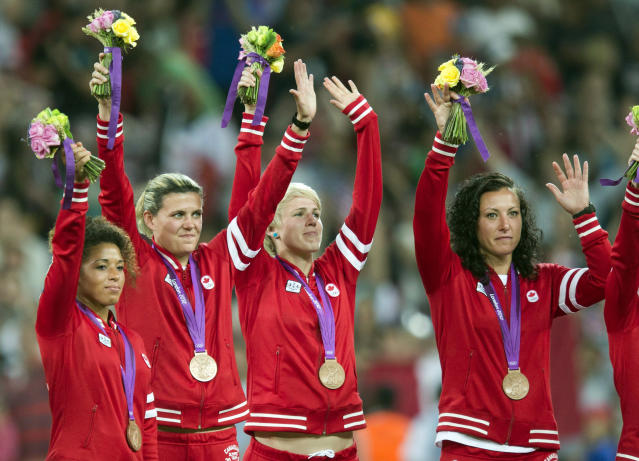 Canada women's soccer team Desiree Scott, (left to right) Christine Sinclair, Sophie Schmidt and Melissa Tancredi wave after being presented with their Bronze medals at the Olympic Games in London on Thursday August 9, 2012. THE CANADIAN PRESS/Frank Gunn