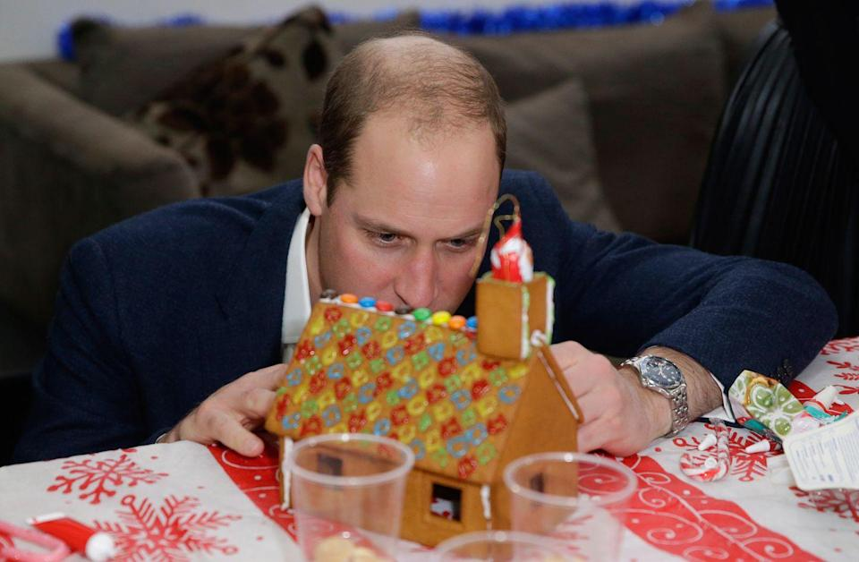 <p>Prince William decorates a gingerbread house at a Christmas party for volunteers of the Mix youth service.</p>
